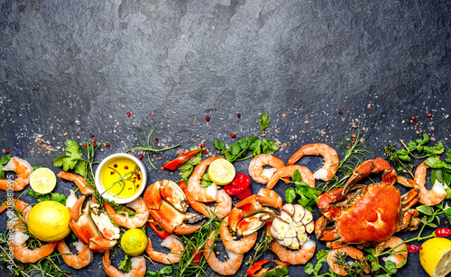 Fototapeta  Fresh raw seafood - shrimps and crabs with herbs and spices on dark gray background