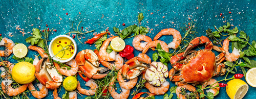 Baner. Fresh raw seafood - shrimps and crabs with herbs and spices on turquoise background. Copy space