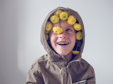 Cheerful Child With Flowers In The Hood