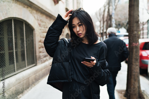 Beautiful asian woman in stylish outfit readjusting the sunglasses on her head while walking the street with a mobile phone in her hand. Hipster girl chatting online while going down the city.