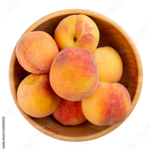Ripe peaches in wooden bowl isolated on white. Top view.