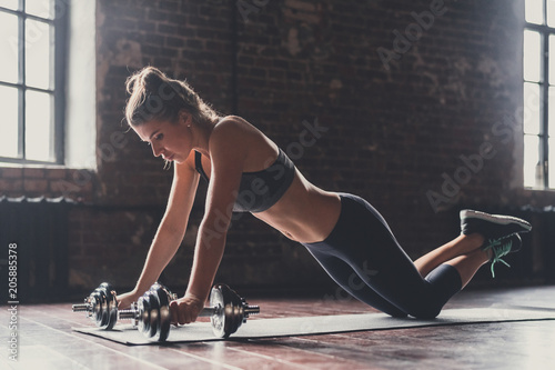 Fotografia  Athletic young girl with dumbbells