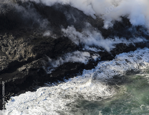Foto op Aluminium Rivier Helicopter aerial view of lava entering the ocean and steam, Big Island, Hawaii.