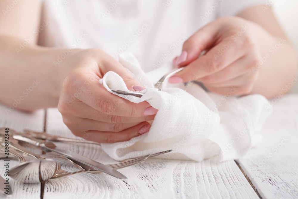 Fototapety, obrazy: Female hand cleaning spotty silverware with a cleaning product and a cloth,Close up woman hand cleaning silver spoon,polished silver