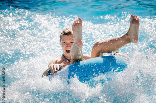 Photo sur Toile Attraction parc Funny girl taking a fast water ride on a float splashing water. Summer vacation with water park concept.