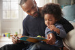 Leinwanddruck Bild - Father And Young Son Reading Book Together At Home