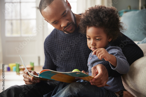 Father And Young Son Reading Book Together At Home Wallpaper Mural