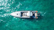 Aerial photo of luxury speed boat docked in tropical island with emerald crystal clear waters