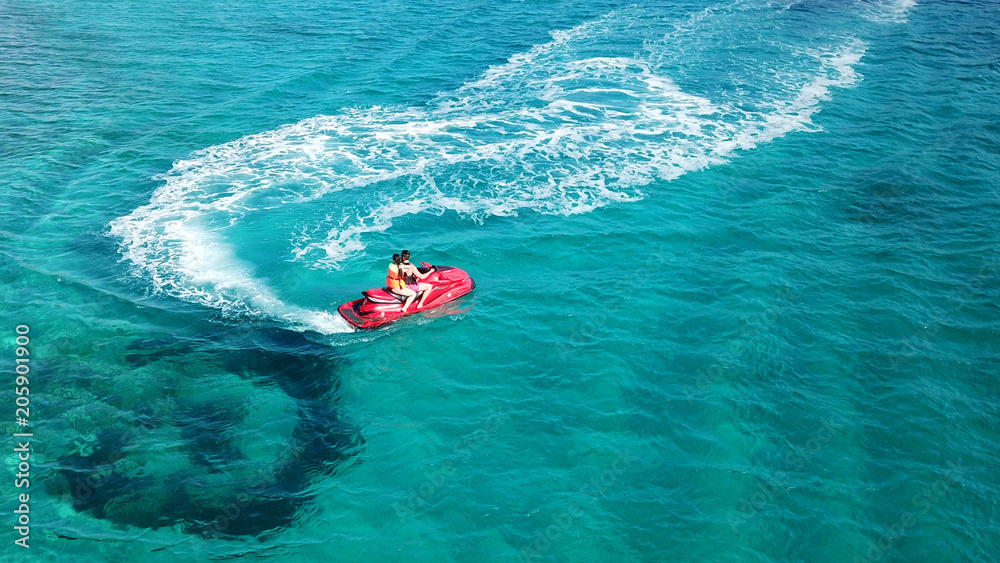 Fototapeta Aerial bird's eye view of jet ski cruising in high speed in turquoise clear water sea