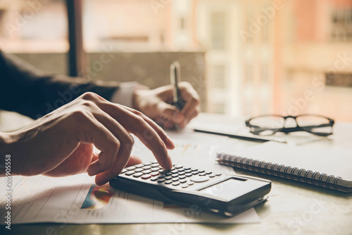 Fotografía  Close up hands businessman doing finances with using calculator and writing note in office