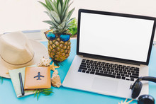 Planning Summer Vacation Concept. Stylish Laptop With Empty Screen, Pineapple In Sunglasses And Passport, Map, Hat, Shells, Notebook On Trendy Blue Paper Table. Travel And Wanderlust