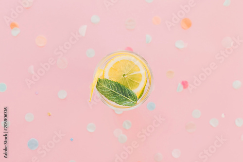Photo  fresh cocktail with lemon and mint in vintage glass on trendy pink paper background with confetti