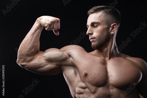 Fotografie, Obraz  Handsome power athletic man bodybuilder demonstrates his biceps.