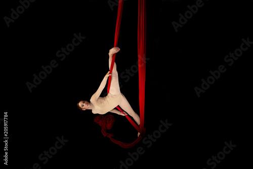 Valokuva  Joven bailarina realizando ejercicios de telas acrobáticas en estudio con fondo