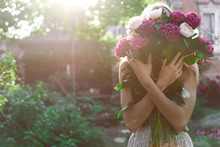 Girl In The Garden With A Big Bouquet Of Peonies In Hands At Sunset