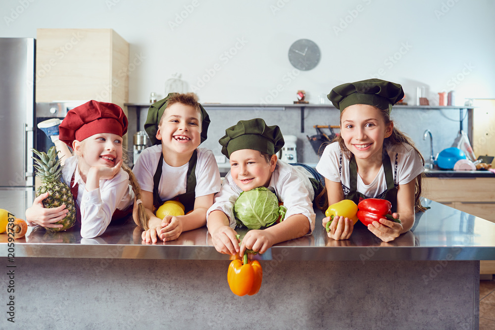Fototapety, obrazy: Funny children in the uniform of cooks on the table in vegetables in the kitchen.