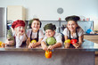 canvas print picture - Funny children in the uniform of cooks on the table in vegetables in the kitchen.