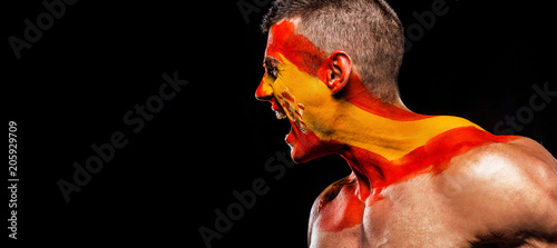 Fotografía  Soccer or football fan with bodyart on face with agression - flag of Spain