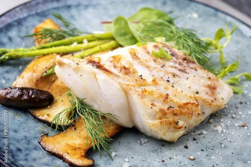Printed kitchen splashbacks Fish Gebratenes Kabeljau Fisch Filet mit grünen Spargel und Pilzen als closeup auf einem Teller
