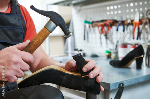Fotografie, Obraz Shoemaker repair female spike shoe. Hammering tip on heel