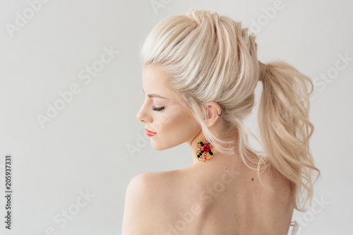 Staande foto Kapsalon Beautiful young woman with a trendy blonde hairstyle, head and shoulders portrait on a grey studio background