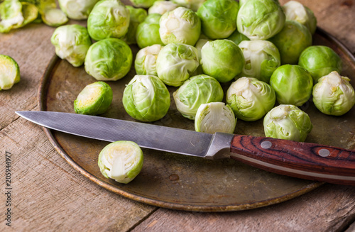Poster Brussel Raw brussels sprouts on rusty steel plate with knife on wooden rustic desk.