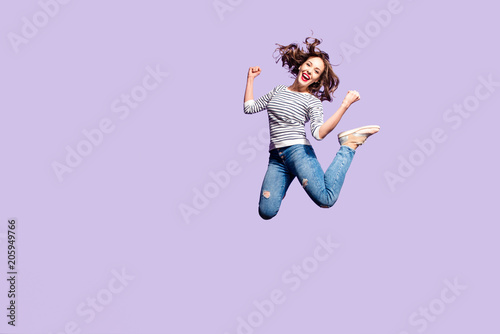 Fotografía  Portrait of successful crazy girl celebrating victory jumping in the air with ra