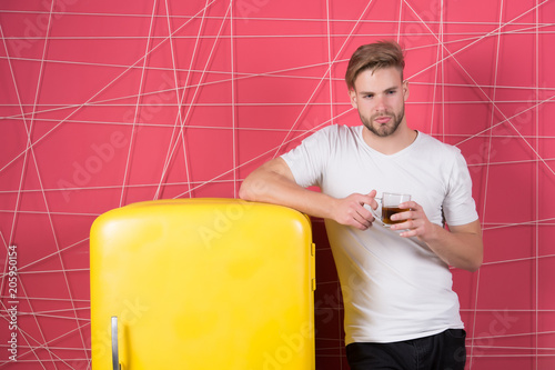 Man keeping cup of tea stands at kitchen leaning on refrigerator