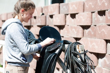 Teenage girl equestrian cleans black Leather Horse Saddle