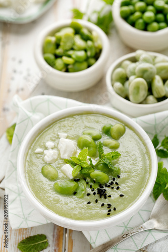 Broad bean soup with fresh mint and feta cheese in a white bowl on a wooden table. Healthy and delicious vegetarian food