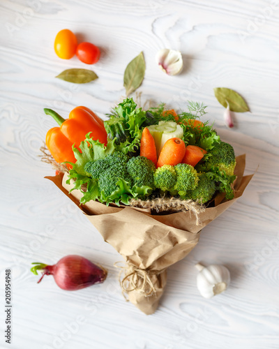 Bouquet of fresh vegetables lies on a white wooden table. Nearby is a red onion, tomatoes, garlic, bay leaf. View from above
