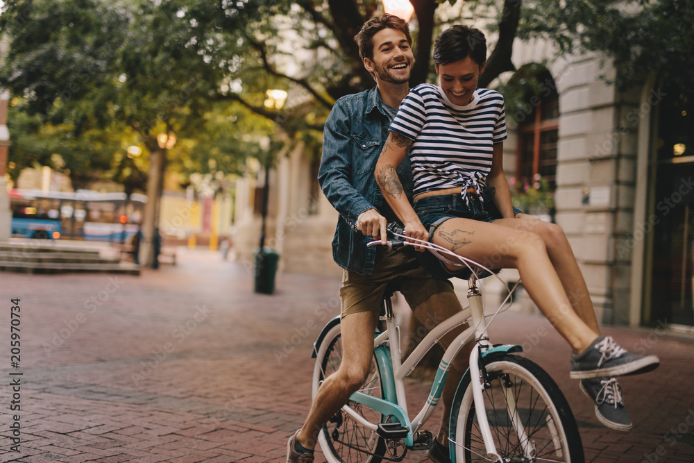 Fototapety, obrazy: Happy couple on a bicycle in the city