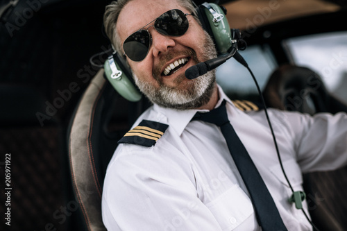 Fényképezés Smiling helicopter pilot with headset