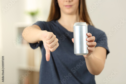 Woman hands holding a soda drink can with thumbs down