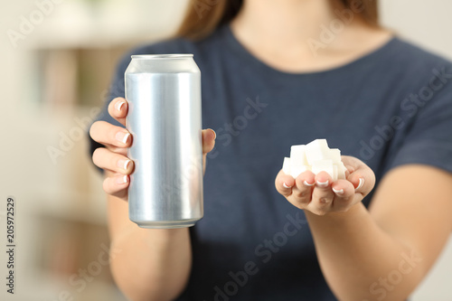 Woman hands holding a soda drink can and sugar cubes