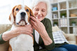 Portrait of happy senior woman lovingly hugging pet dog and smiling while enjoying weekend at home sitting on comfortable couch in modern apartment with her furry friend.