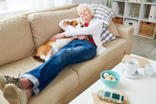 Full Length High Angle Portrait Of White Haired Senior Woman Sleeping On Couch Hugging Her Dog Enjoying Afternoon Nap At Home, Copy Space