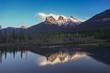 Scenic Landscape View of Snowcapped Three Sisters Mountain reflected in calm water, Alberta Foothills Canadian Rockies