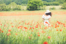 Woman With White Dress In A Poppy Field During Summer
