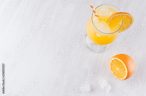 In de dag Cocktail Colorful orange cool citrus cocktail with slice oranges, ice cube, straw on white modern wooden background, top view.