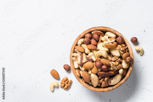 Fotomural  Nuts assortment in a bowl on white top view.