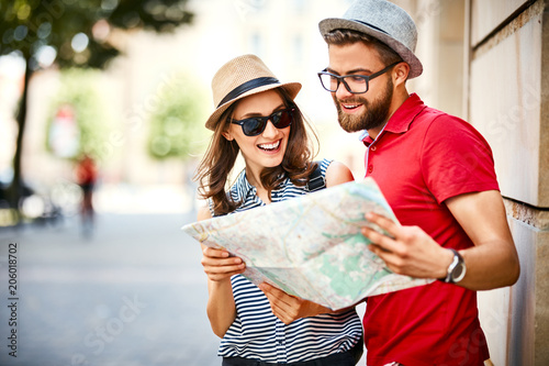 Young couple looking at map while on vacation during summer together - fototapety na wymiar
