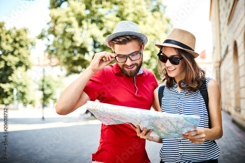 Fotografie, Obraz Young couple on vacation looking at map outdoors