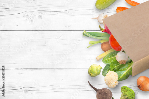 Paper bag with fresh market vegetables on whitee wooden table with copy space.
