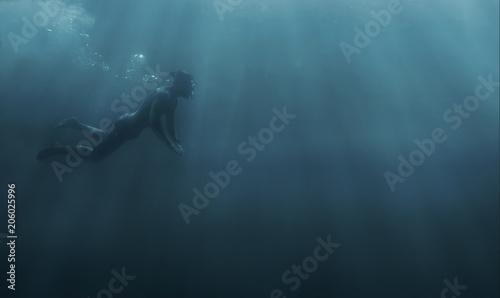 Male freediver snorkeling in deep sea.