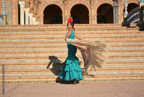 The beautiful girl in the green flamenco dress dances the flamenco in plaza de España,