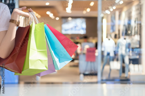 Fotografering Closeup of woman holding shopping colorful of shopping bags at shopping mall wit