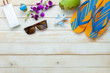 Table top view aerial image of summer & travel beach holiday in the season background concept.Flat lay sun block protection lotion & decoration for traveler on modern plank white wood and copy space.