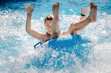 Funny Girl Taking A Fast Water Ride On A Float Splashing Water. Summer Vacation With Water Park Concept.