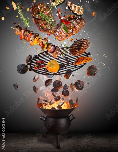 Aluminium Prints Grill / Barbecue Kettle grill with hot briquettes, cast iron grate and tasty skewers flying in the air.